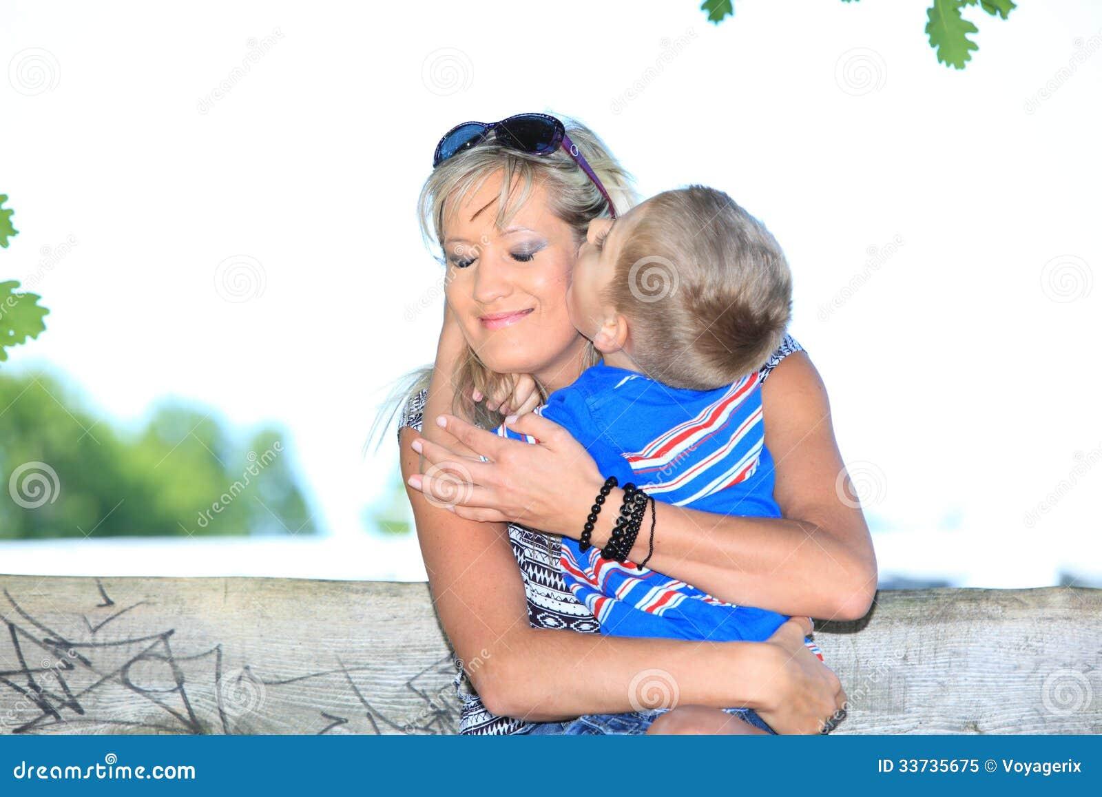 Счастливые мать и сын семьи на стенде в парке