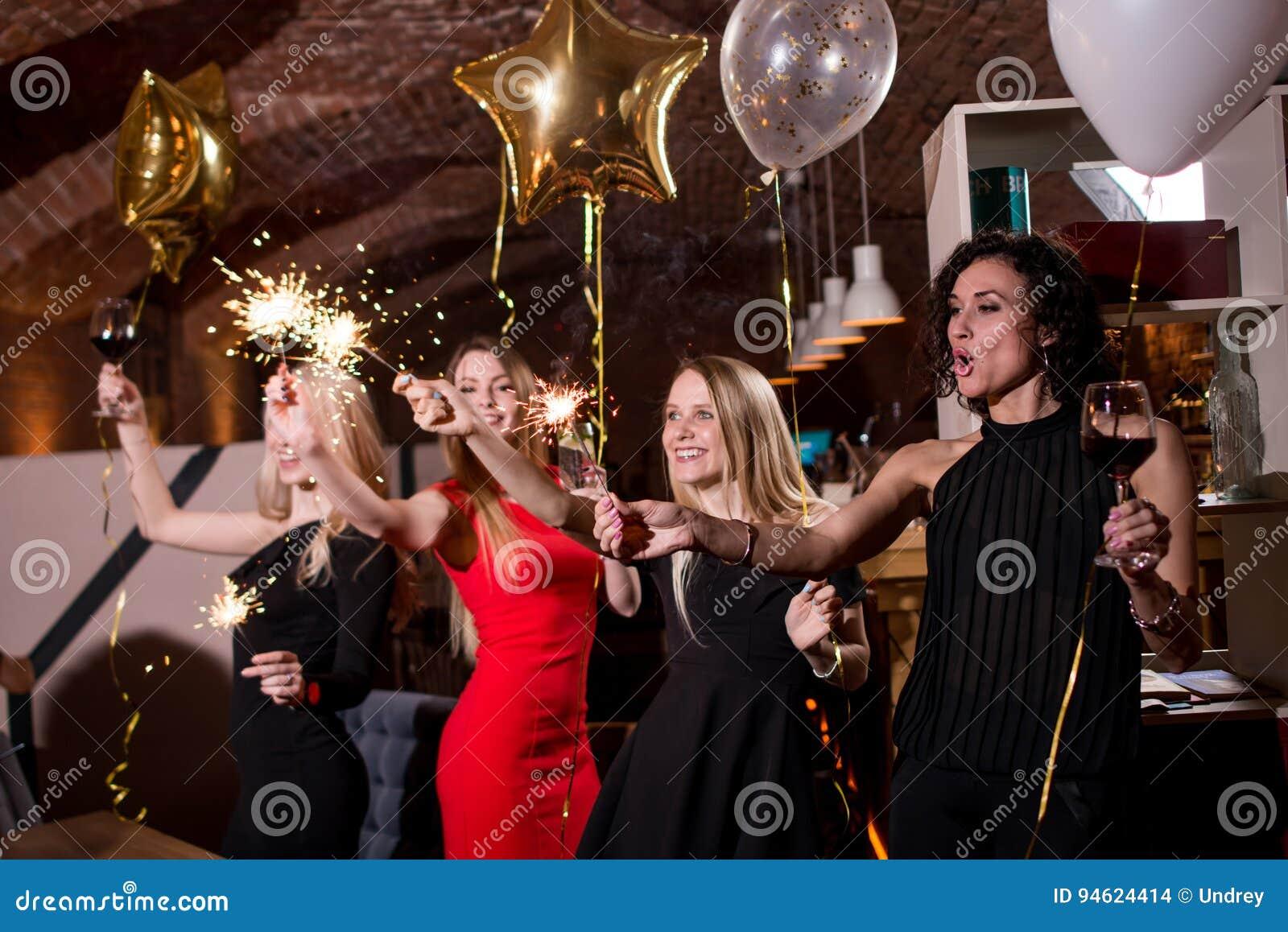 Счастливые милые молодые женщины держа бенгальские огни фейерверка, воздушные шары, стекла вина празднуя праздник в ресторане с