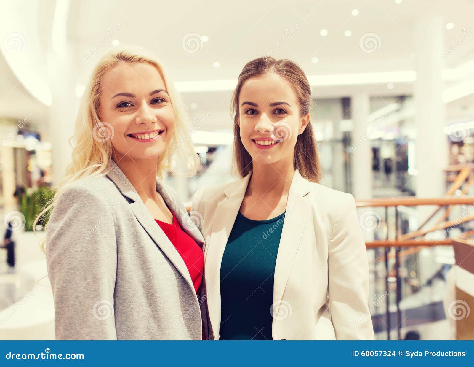 Счастливые молодые женщины в моле или деловом центре