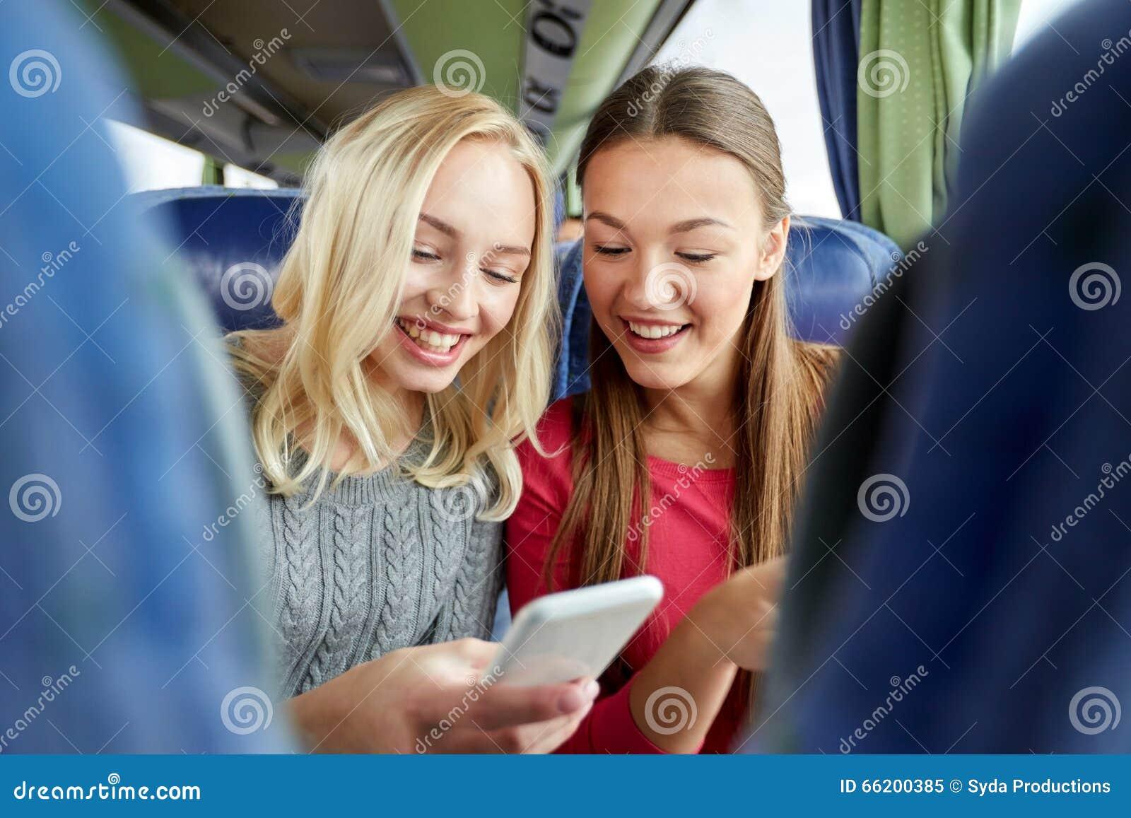 Счастливые молодые женщины в шине перемещения с smartphone