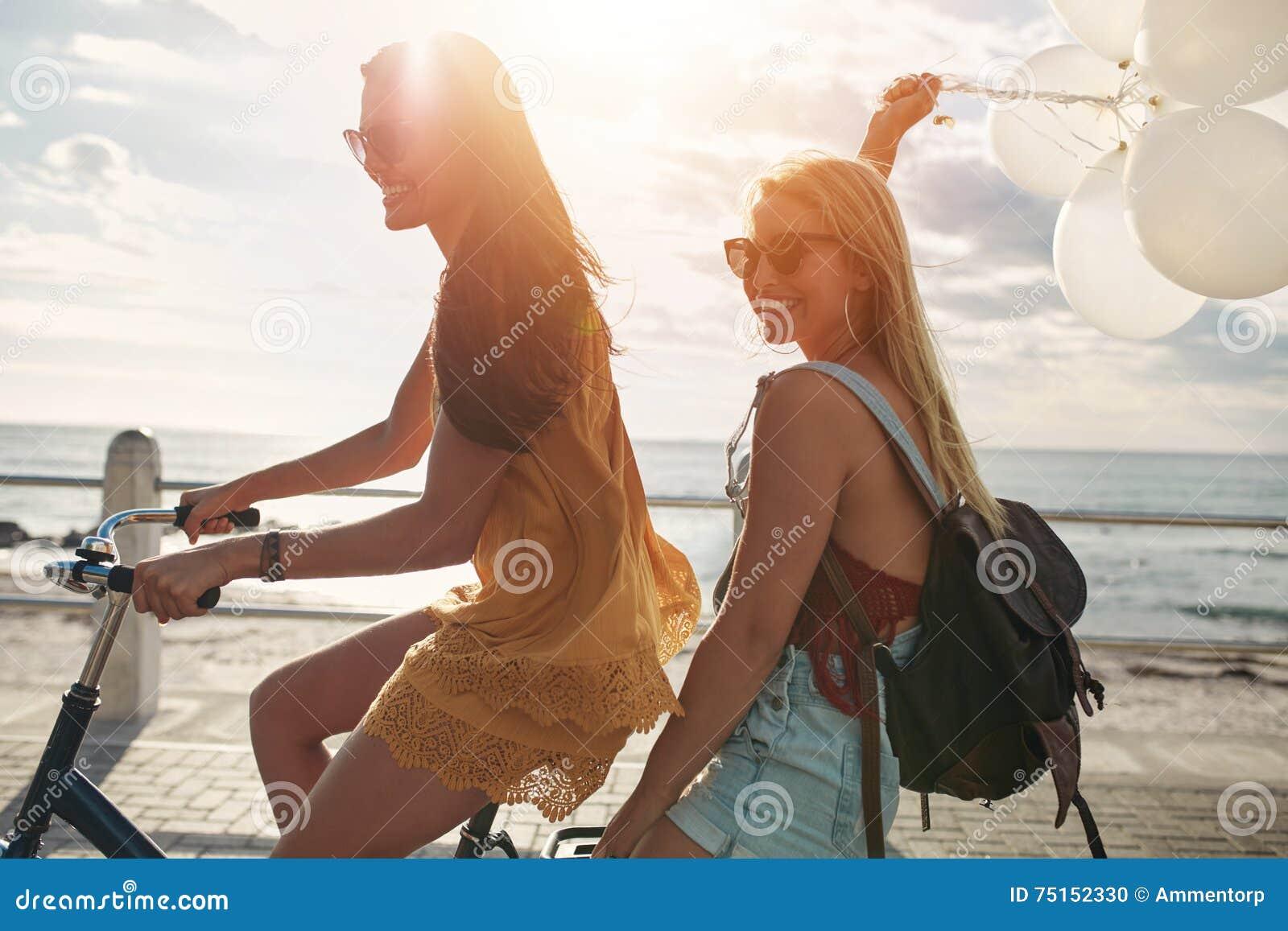 Счастливые молодые женщины на велосипеде вместе с воздушными шарами