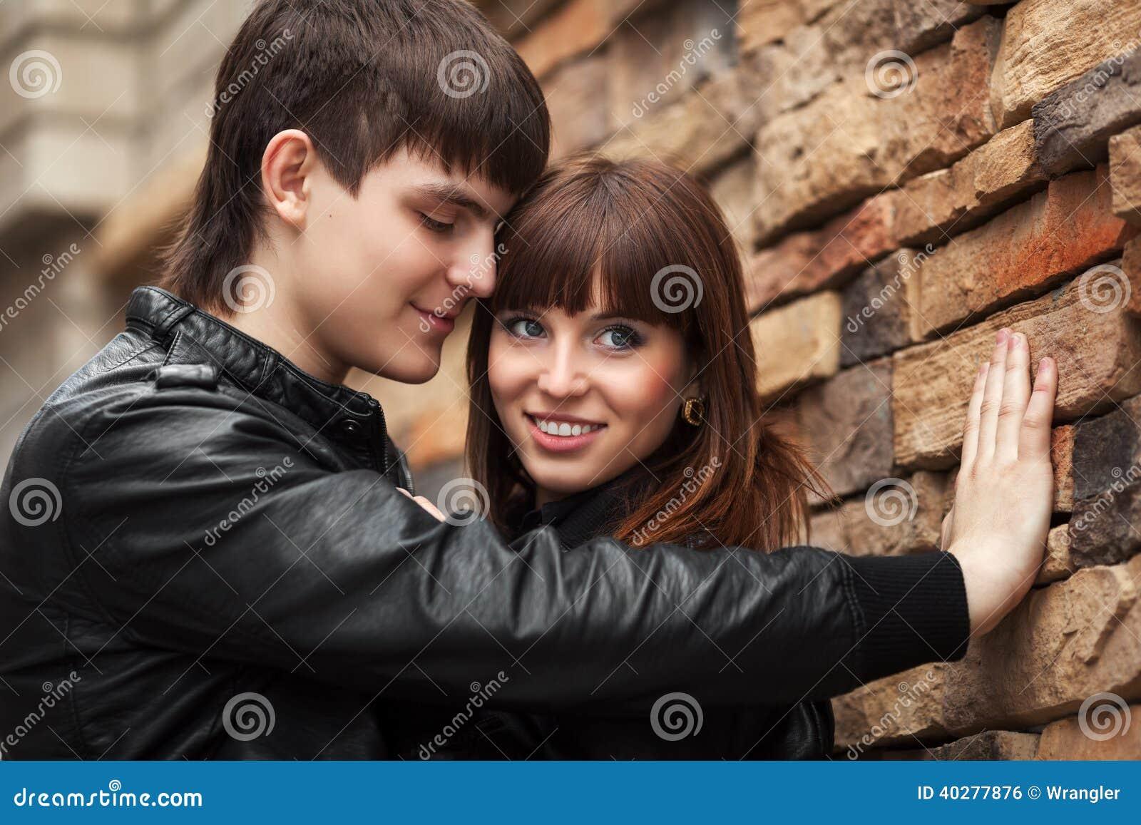 Счастливые молодые пары в влюбленности на кирпичной стене