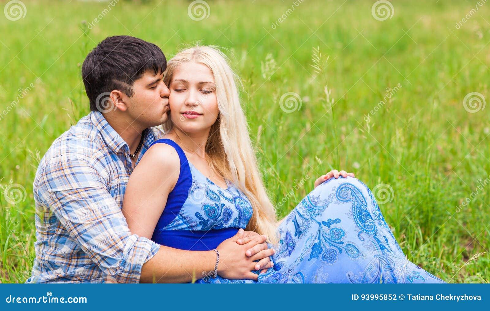 Счастливые молодые пары ослабляя на лужайке в лете паркуют человек влюбленности поцелуя принципиальной схемы к женщине Каникулы