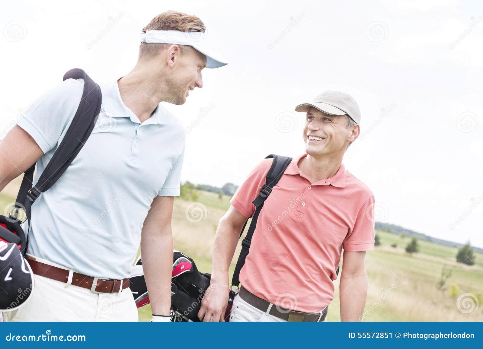 Счастливые мужские игроки в гольф беседуя против ясного неба