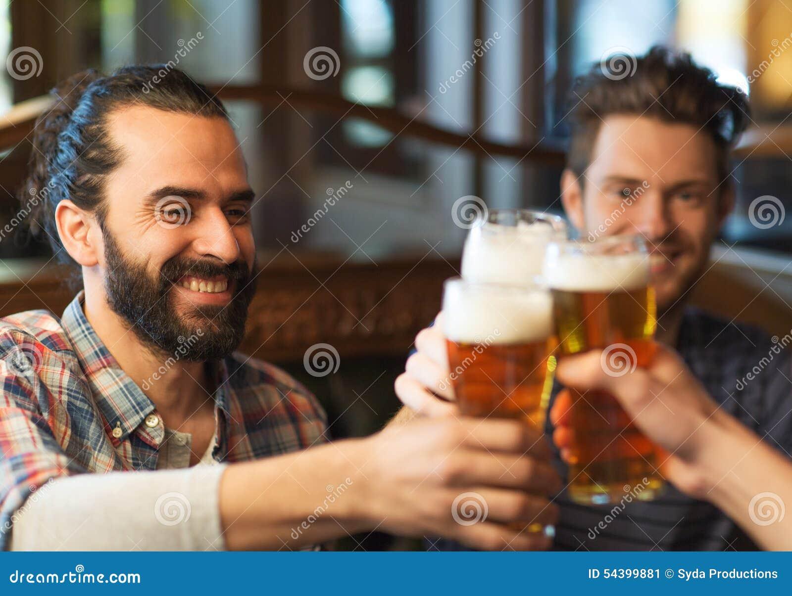 Счастливые мужские друзья выпивая пиво на баре или пабе
