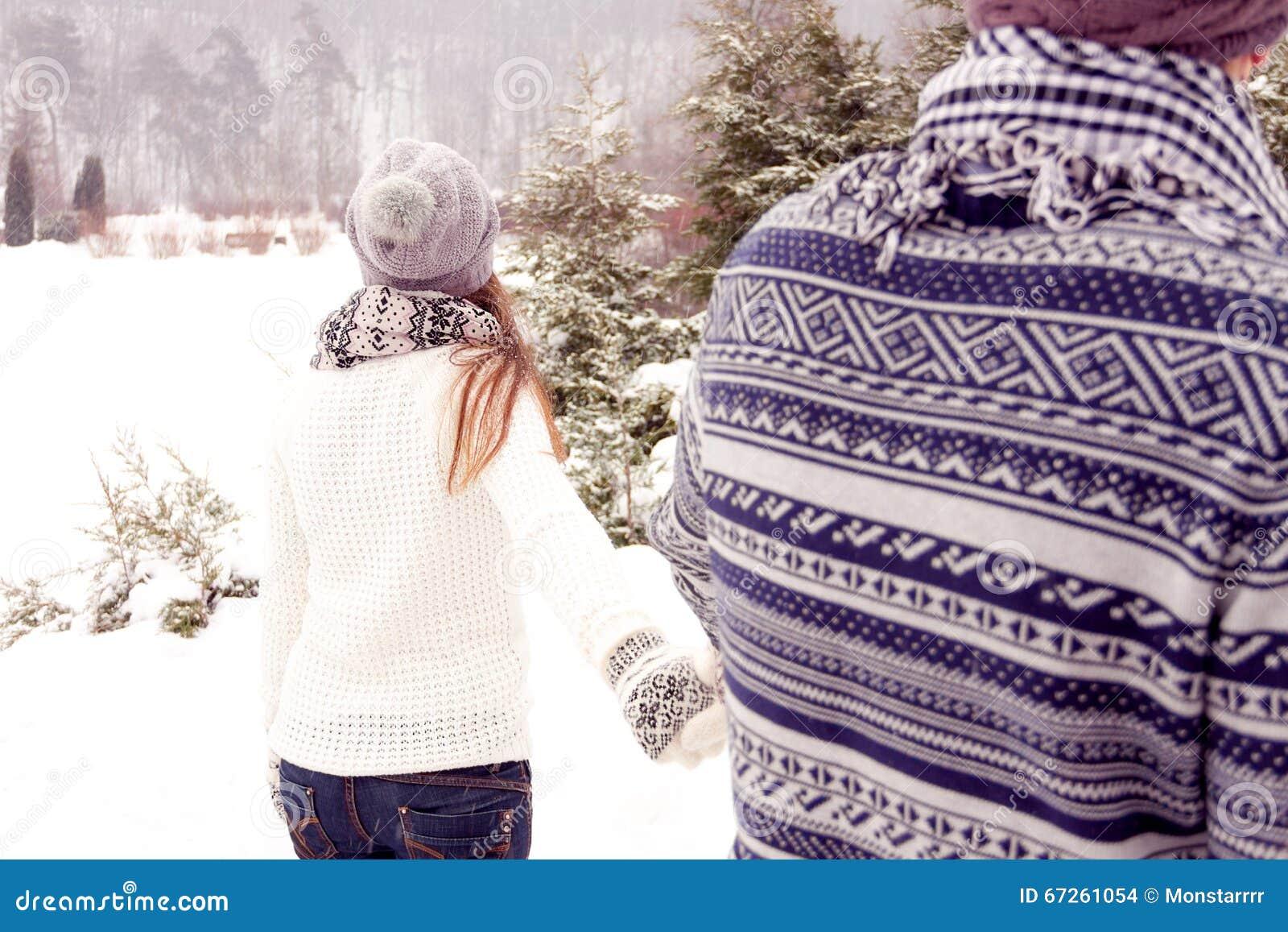 Счастливые пары в влюбленности идя прочь в парк в зиме