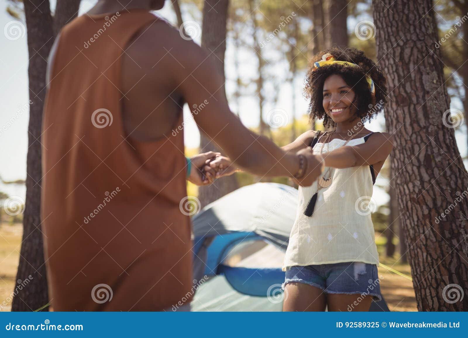 Счастливые пары держа руки пока стоящ против шатра