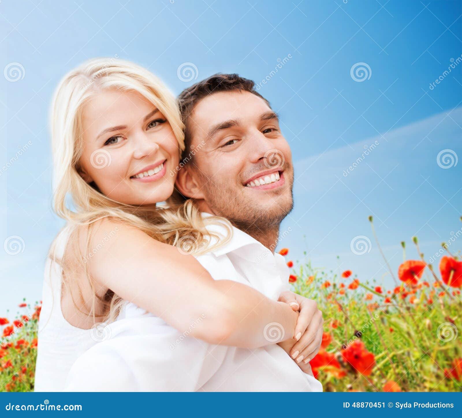 Счастливые пары имея потеху над полем цветков мака