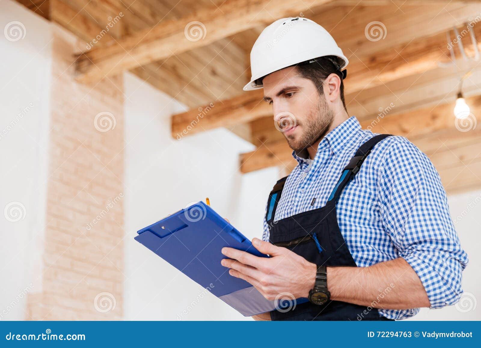 Download Счастливые примечания сочинительства построителя в защитном шлеме с доской сзажимом для бумаги Стоковое Изображение - изображение насчитывающей конструкция, профессионал: 72294763