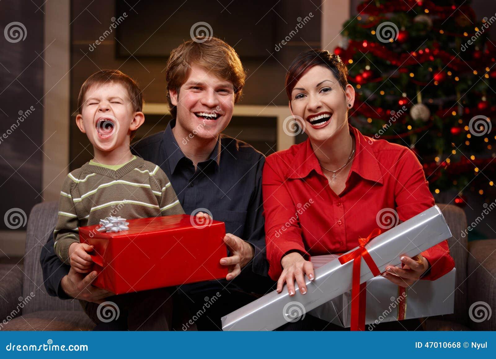 Счастливые родители и сын с подарками рождества