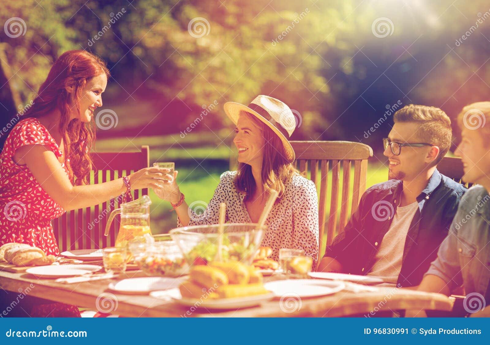 Счастливые друзья имея обедающий на приём гостей в саду лета