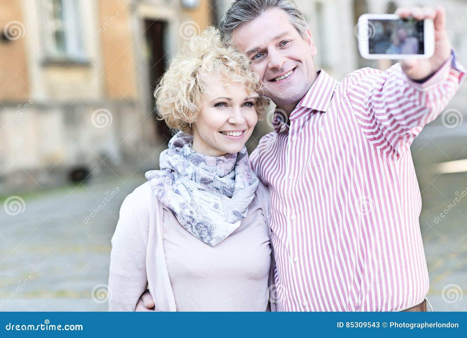 Счастливые средн-постаретые пары принимая selfie через умный телефон в городе