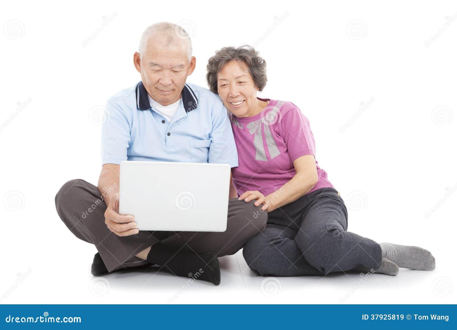 Счастливые старшие пары наблюдая или полагаясь с компьтер-книжкой