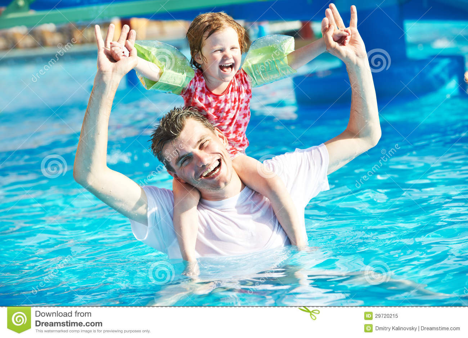 Отец и ребенок в плавательном бассеине курорта