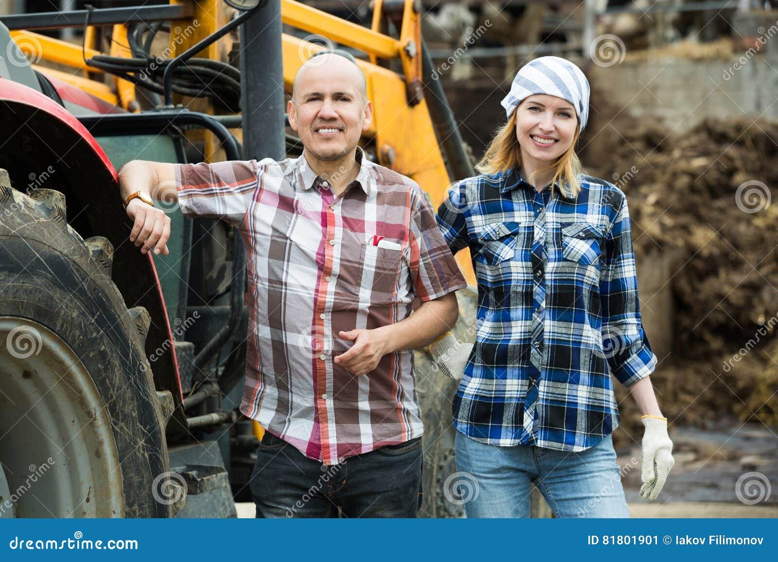 Счастливые фермеры работая на машинном оборудовании