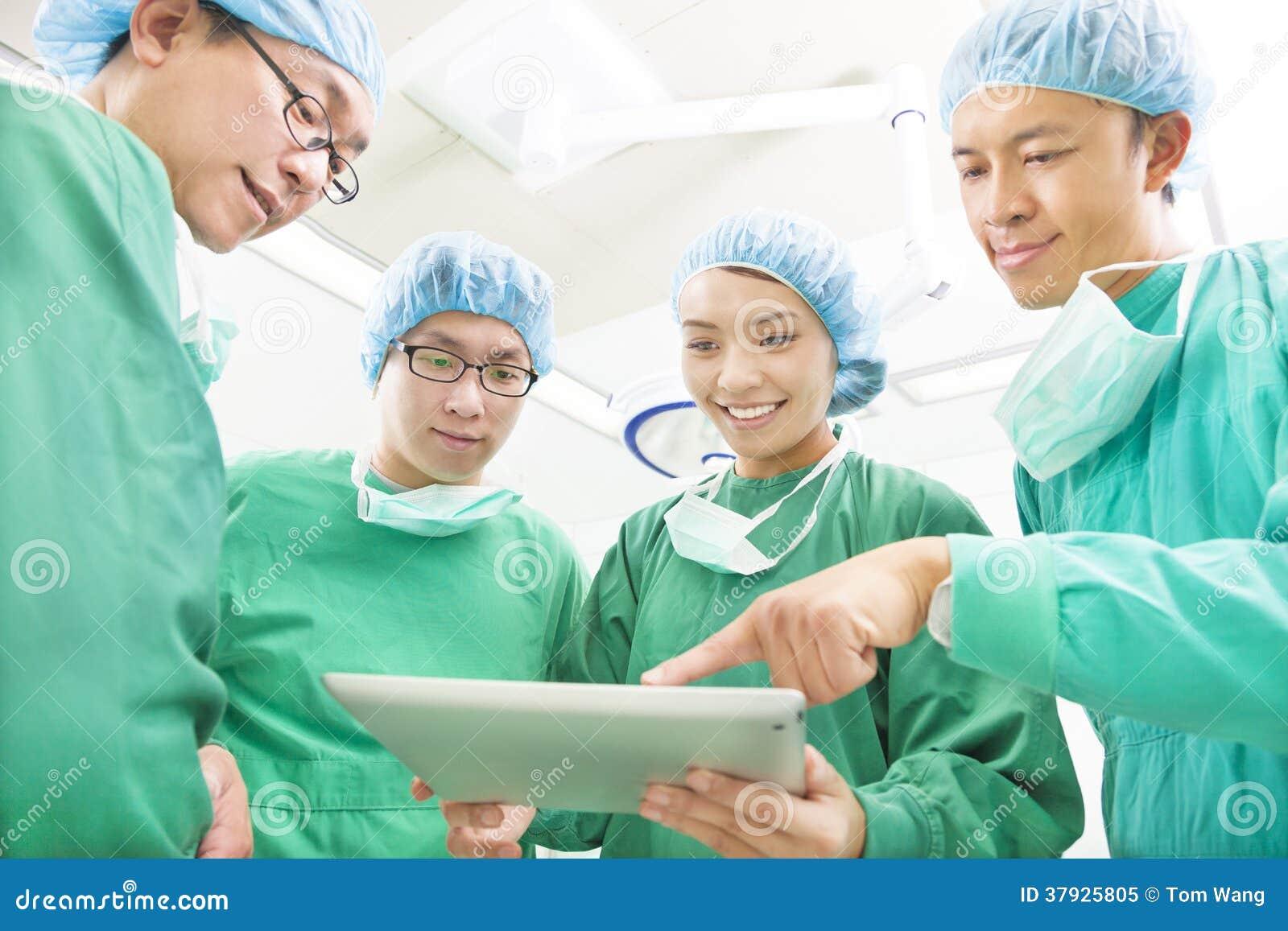 Счастливые хирурги обсуждая метод работы успеха