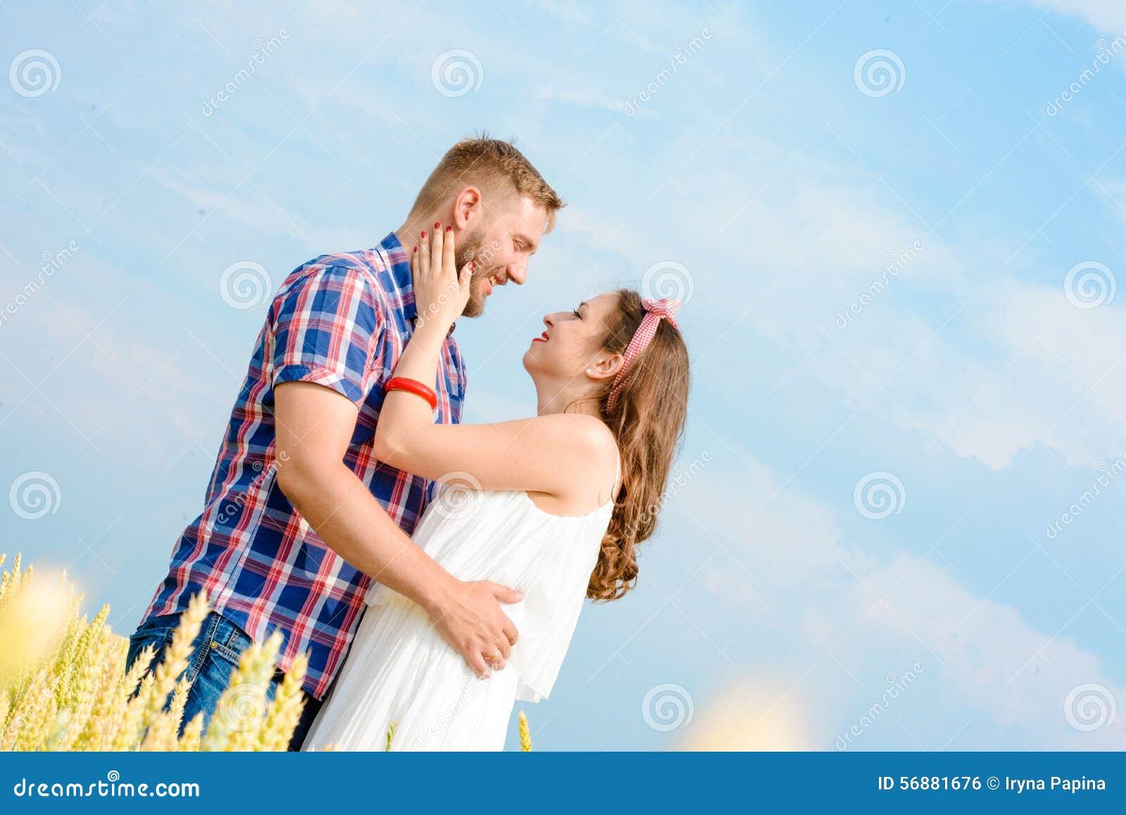 Счастливые любящие молодые взрослые пары тратя время на поле на солнечный день