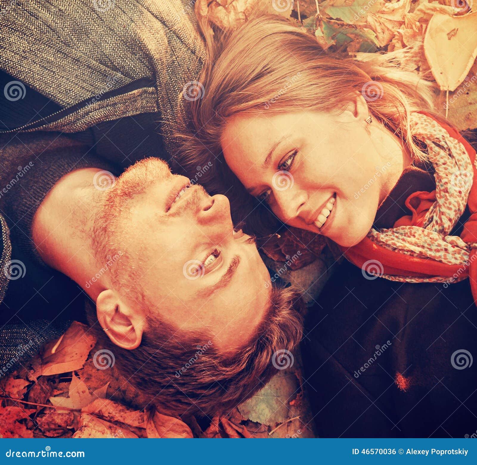 Счастливые любящие пары лежа на листьях осени, конец-вверх