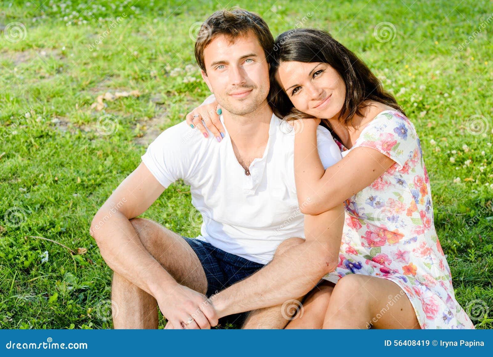 Счастливые любя усмехаясь молодые пары outdoors