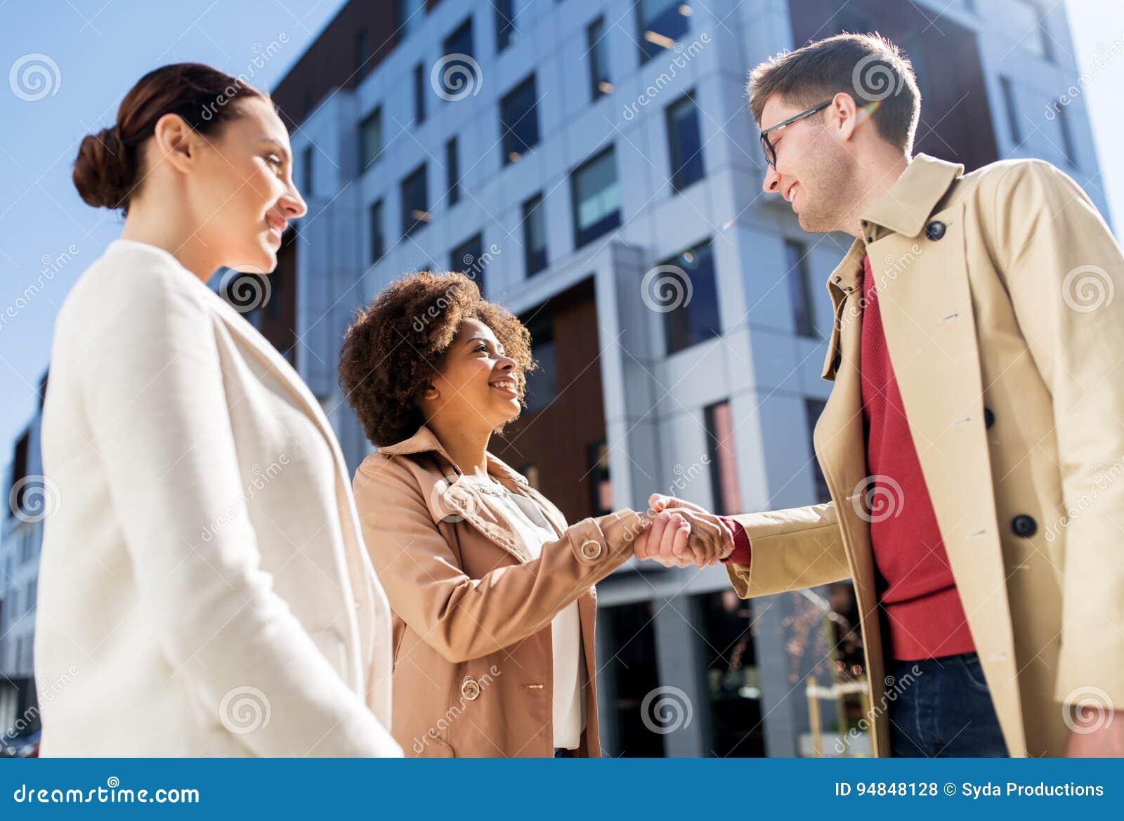 Счастливые люди тряся руки на улице города