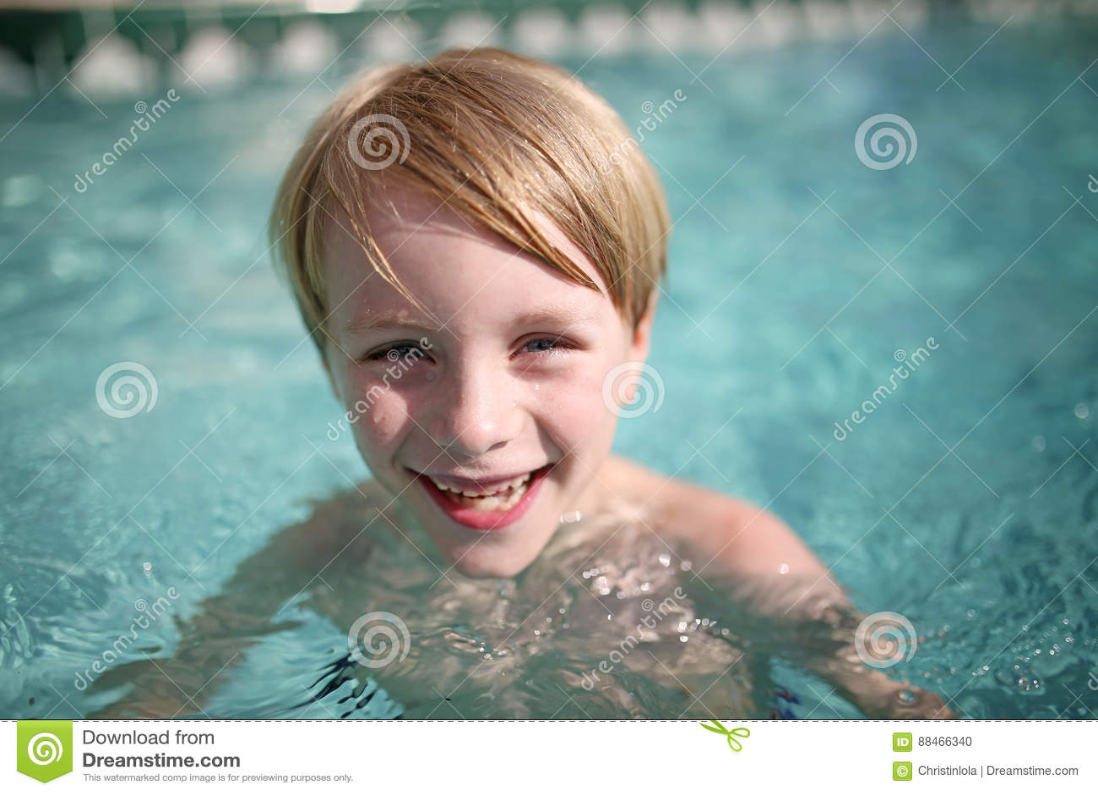 Счастливый маленький ребенок смеясь над в бассейне