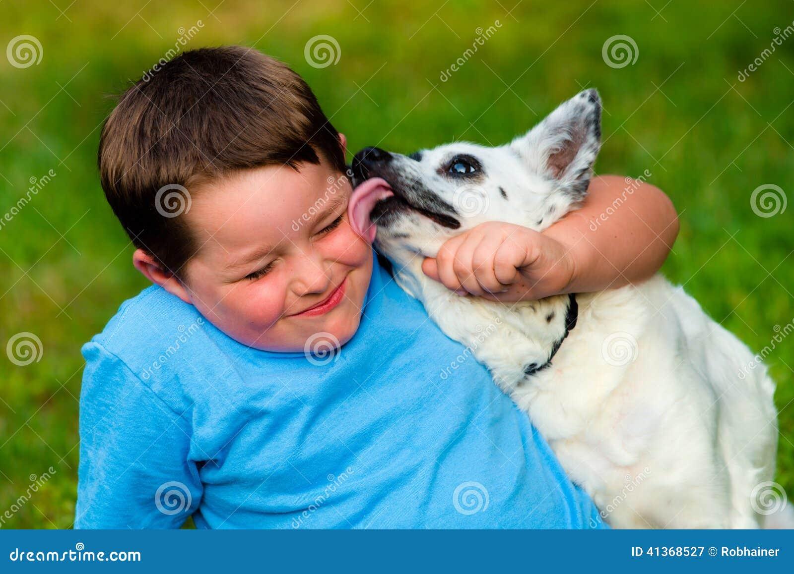 Счастливый мальчик будучи вылизанным его любимчиком