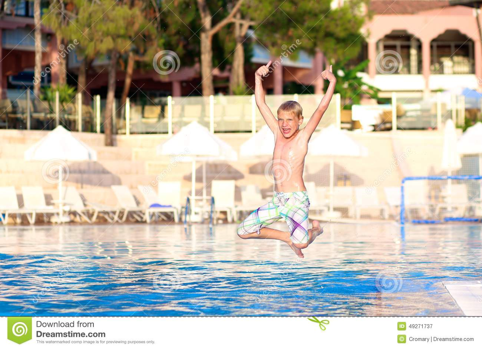Счастливый мальчик скача в бассейн