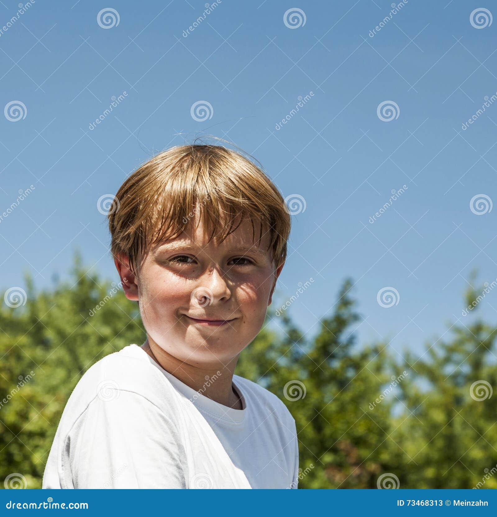 Счастливый мальчик усмехается и наслаждается жизнью