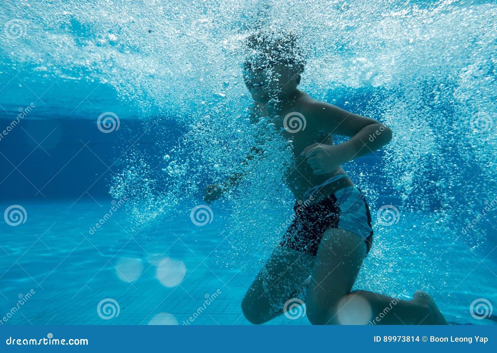 Счастливый молодой азиатский ребенк с изумлёнными взглядами заплыва подводными