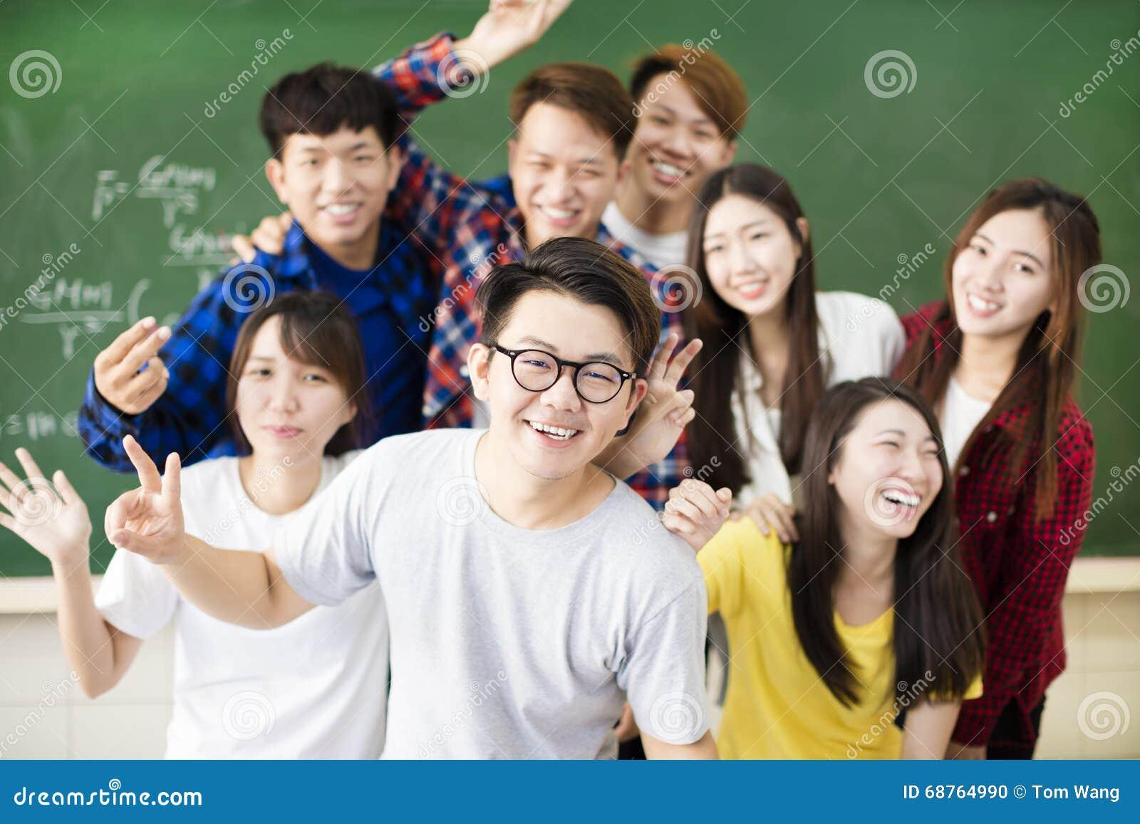 Счастливый молодой студент колледжа группы в классе