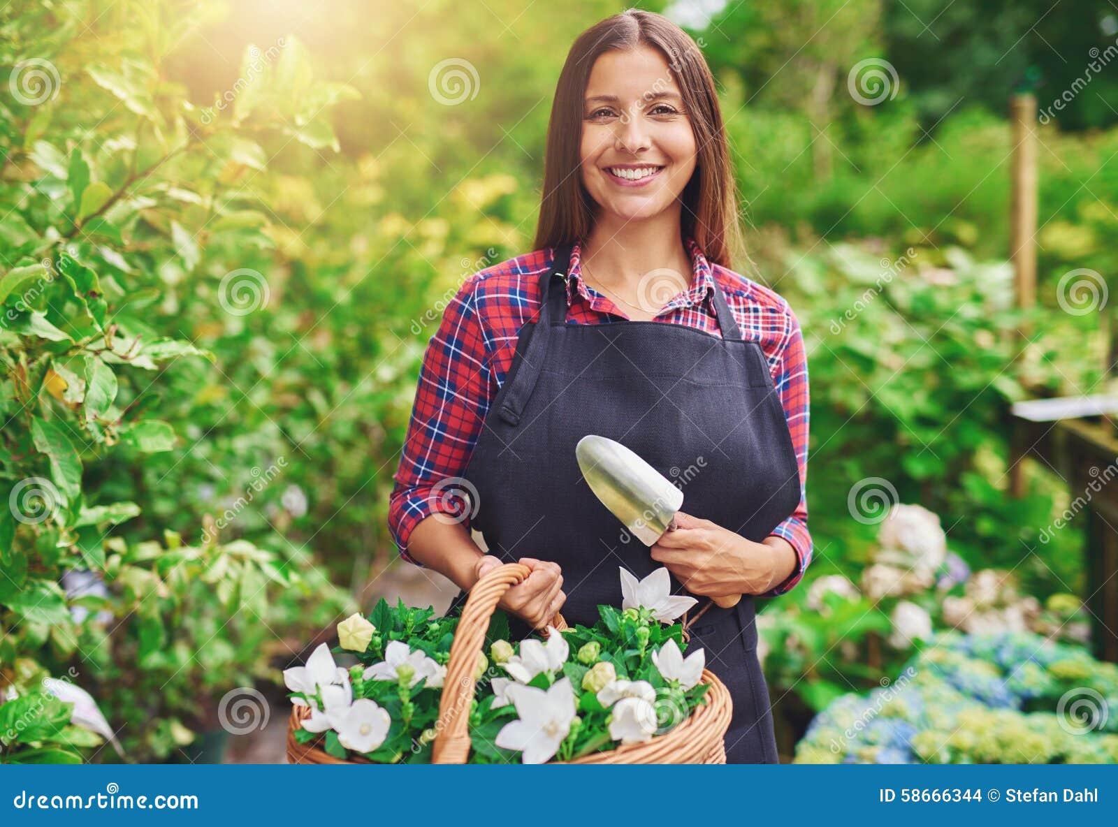 Счастливый молодой флорист работая в парнике