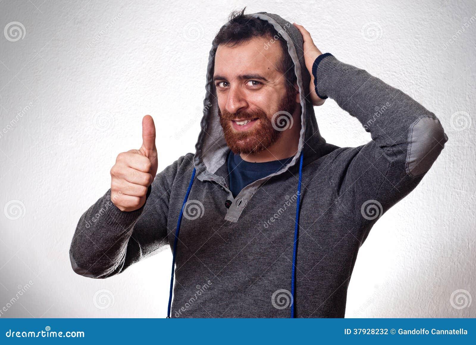 Счастливый молодой человек показывая большой палец руки вверх по знаку