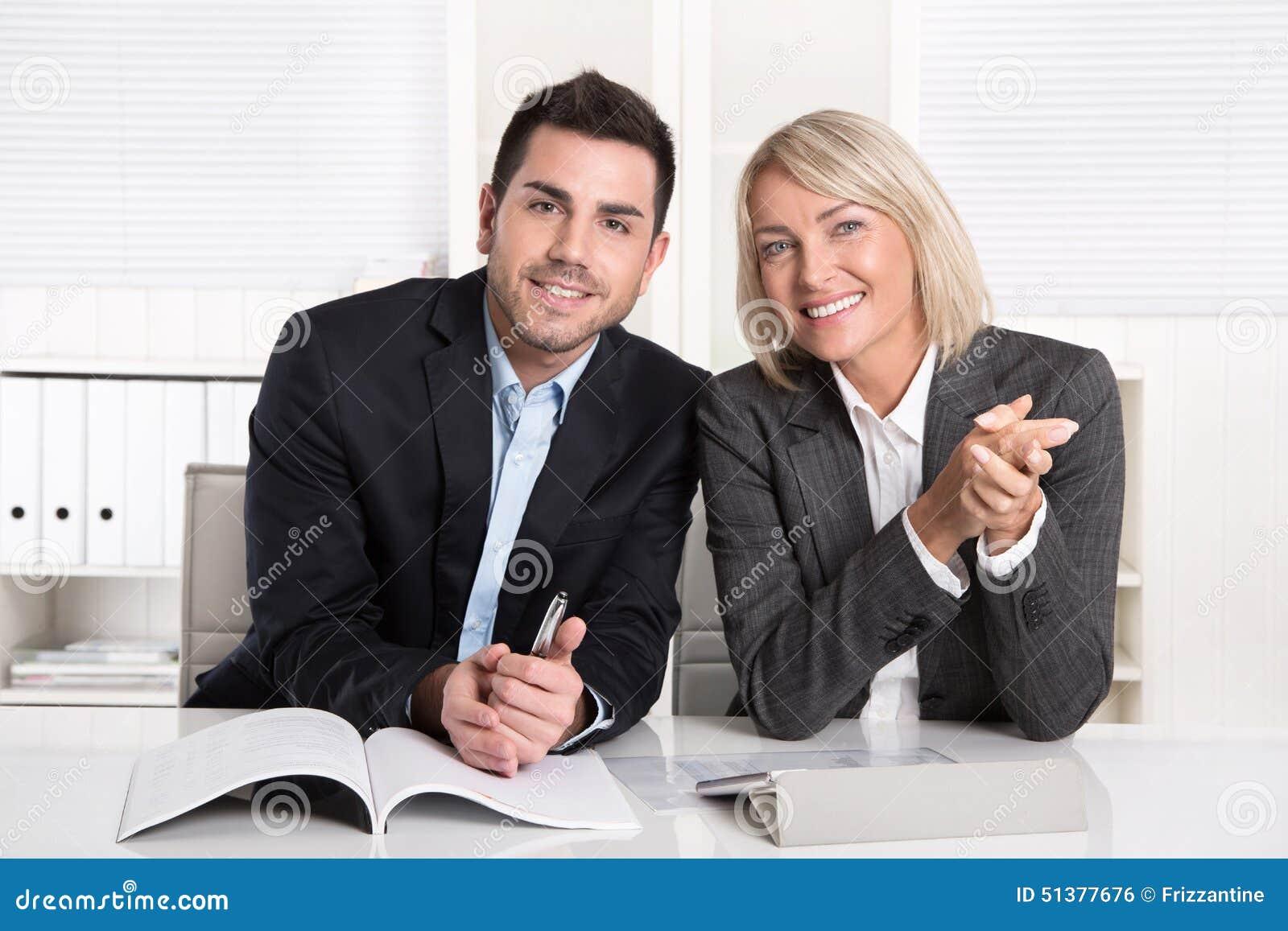 Счастливый мужчина и женское дело объединяются в команду сидеть в офисе Succe