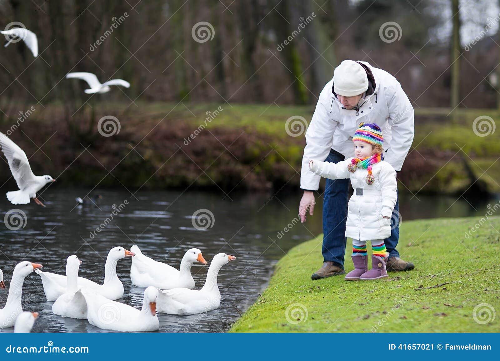 Счастливый отец и его гусыни дочери малыша подавая