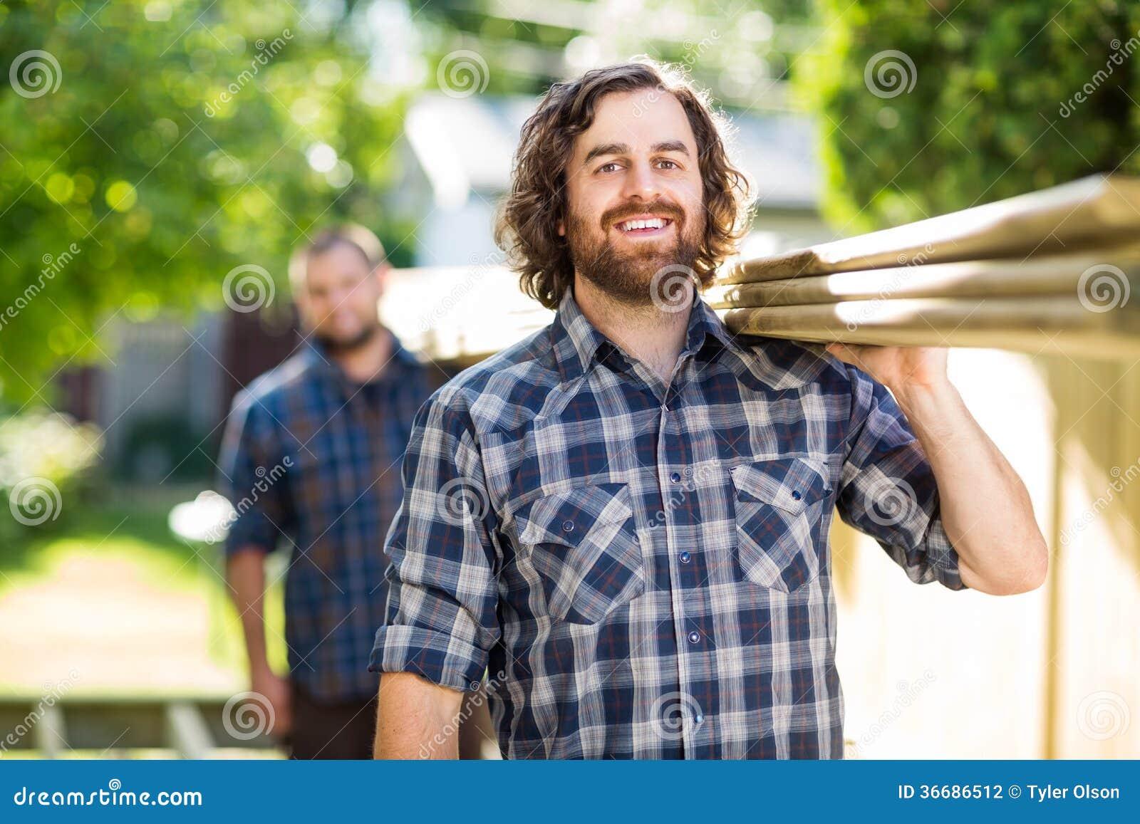 Счастливый плотник с планками нося сотрудника