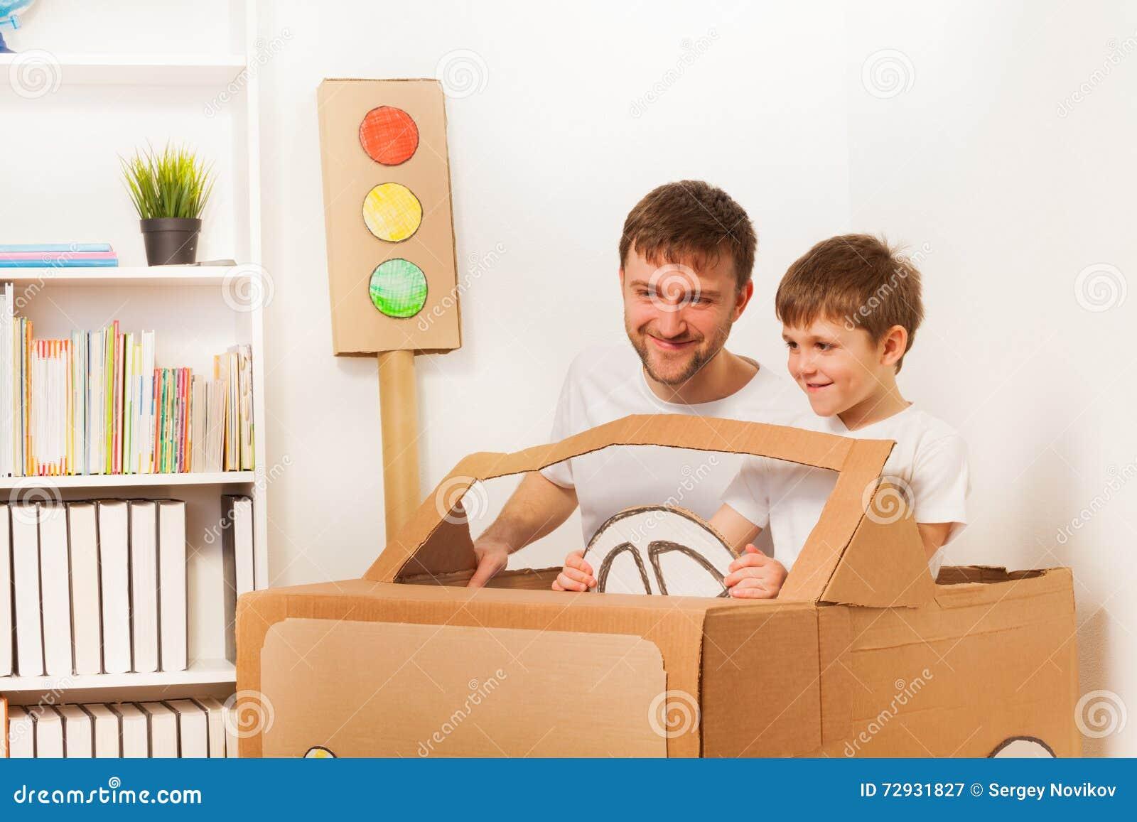Счастливый ребенк и его папа управляя автомобилем картона игрушки