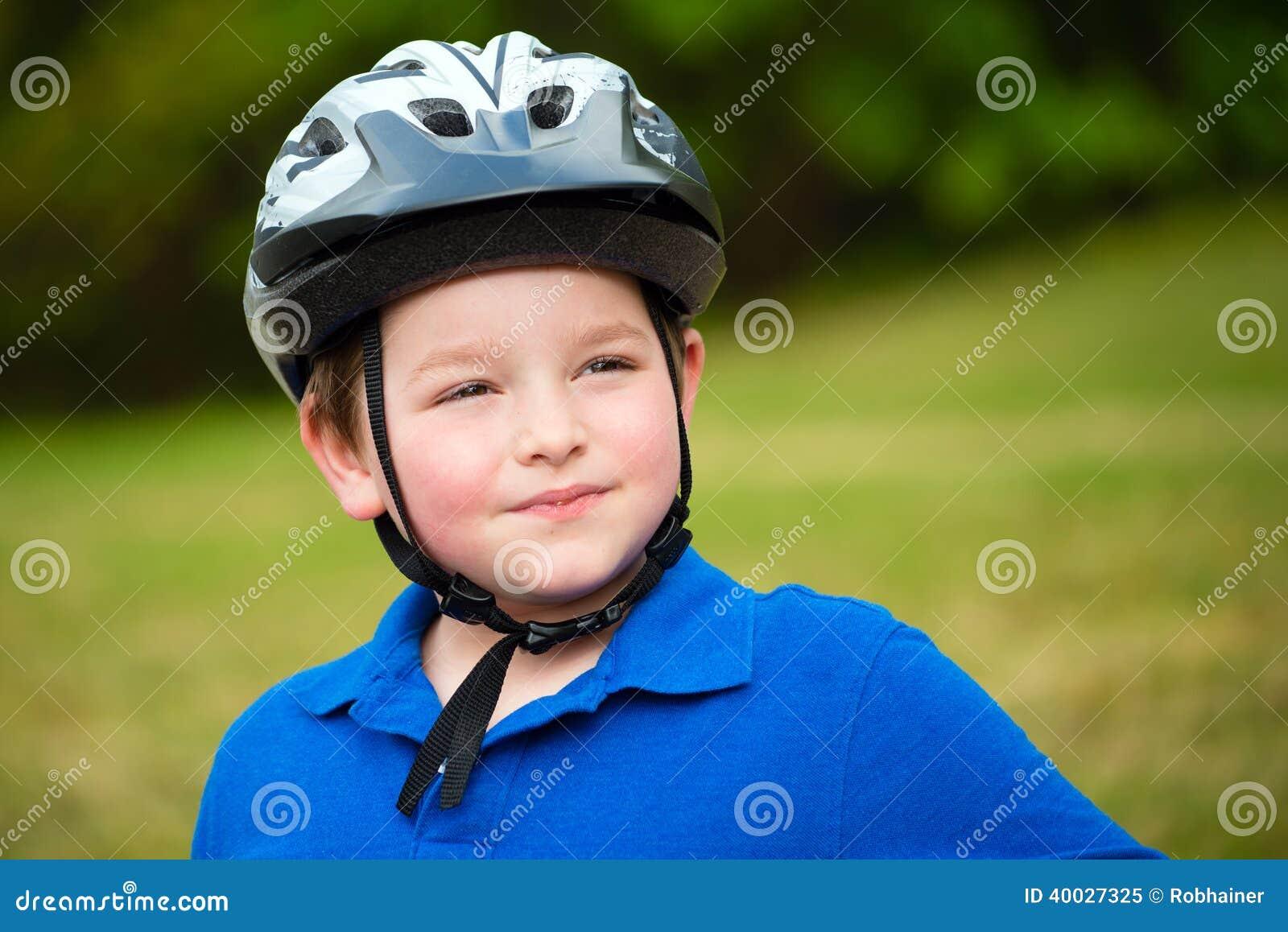 Счастливый ребенок нося шлем велосипеда