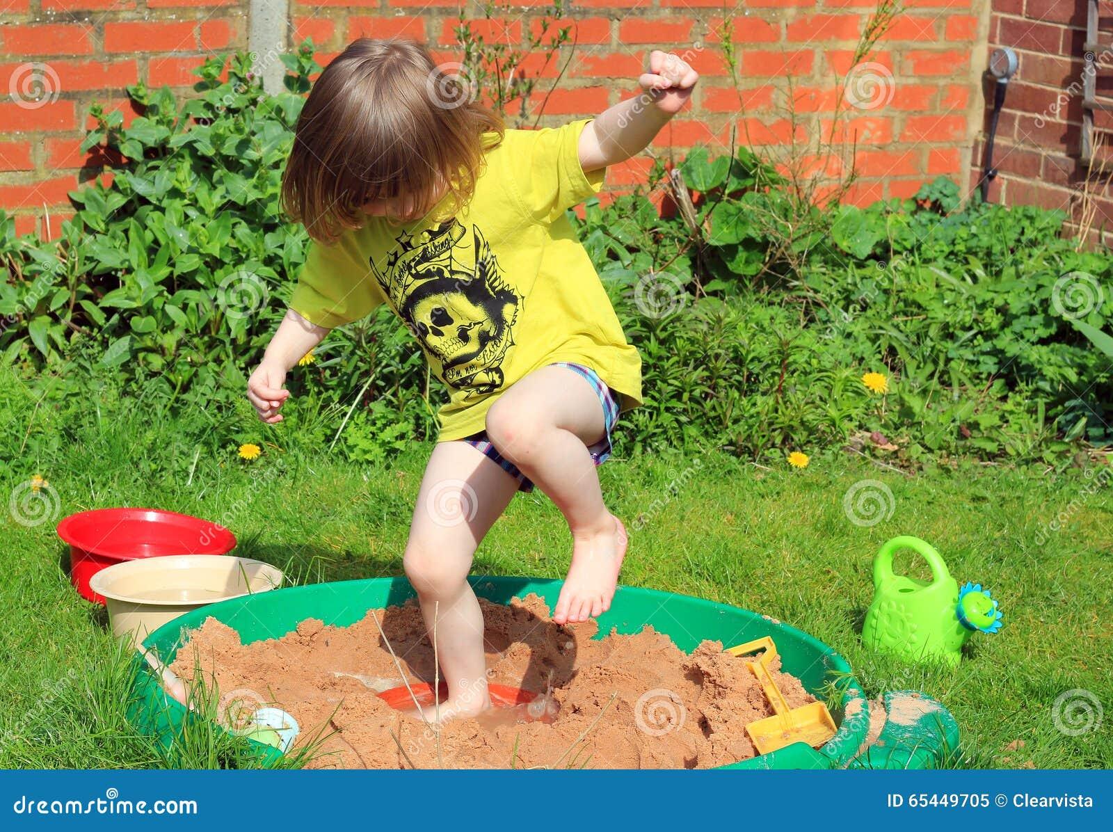 Счастливый ребенок скача в яму песка