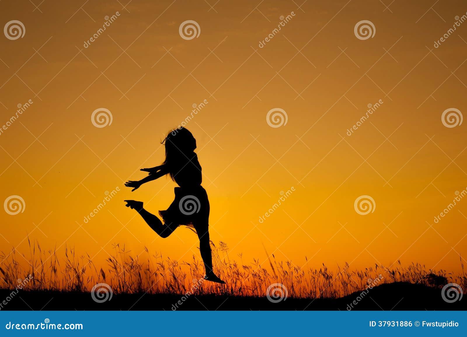 Счастливый силуэт скакать и захода солнца женщины