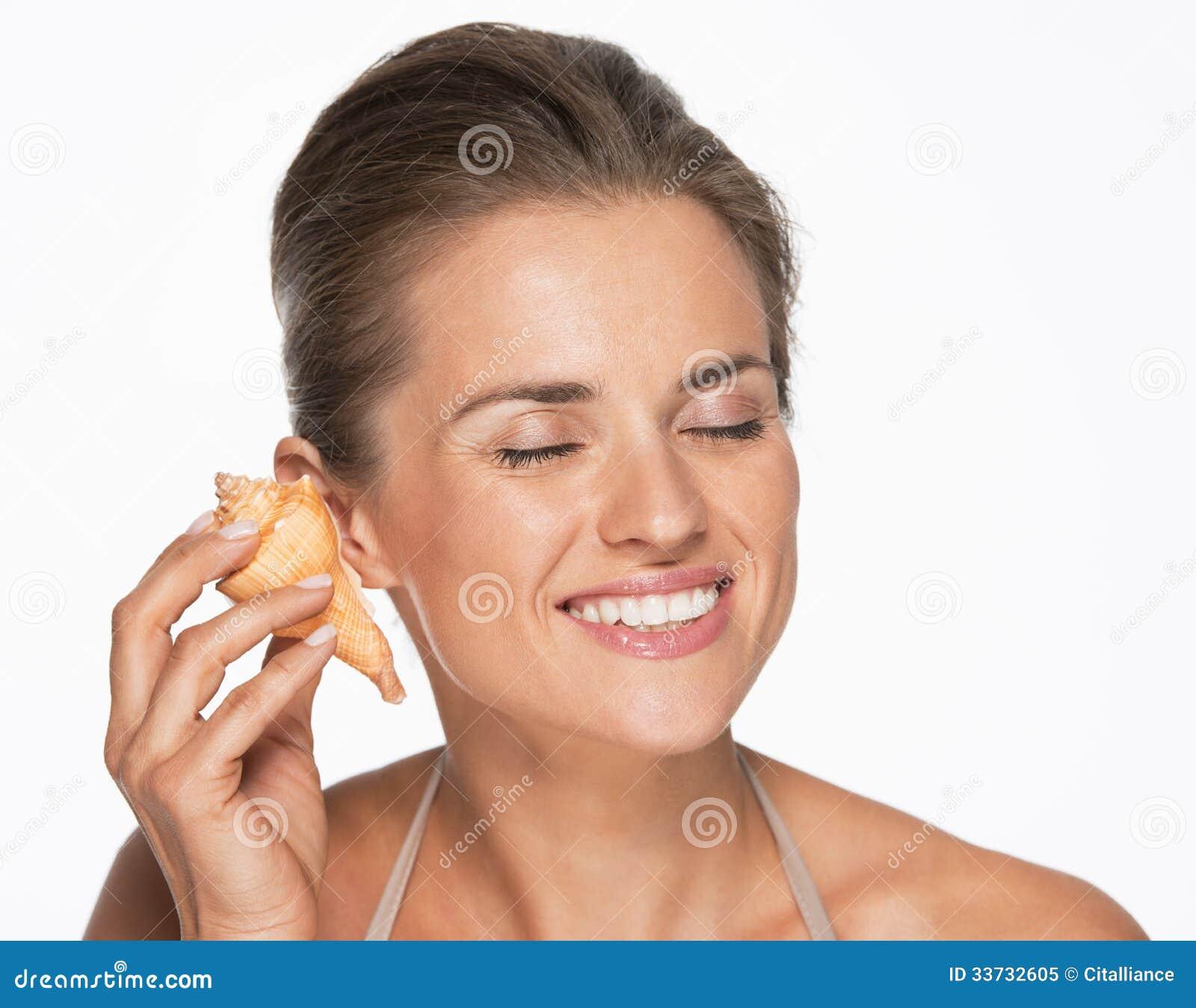 Счастливый слух женщины развевает в раковине моря