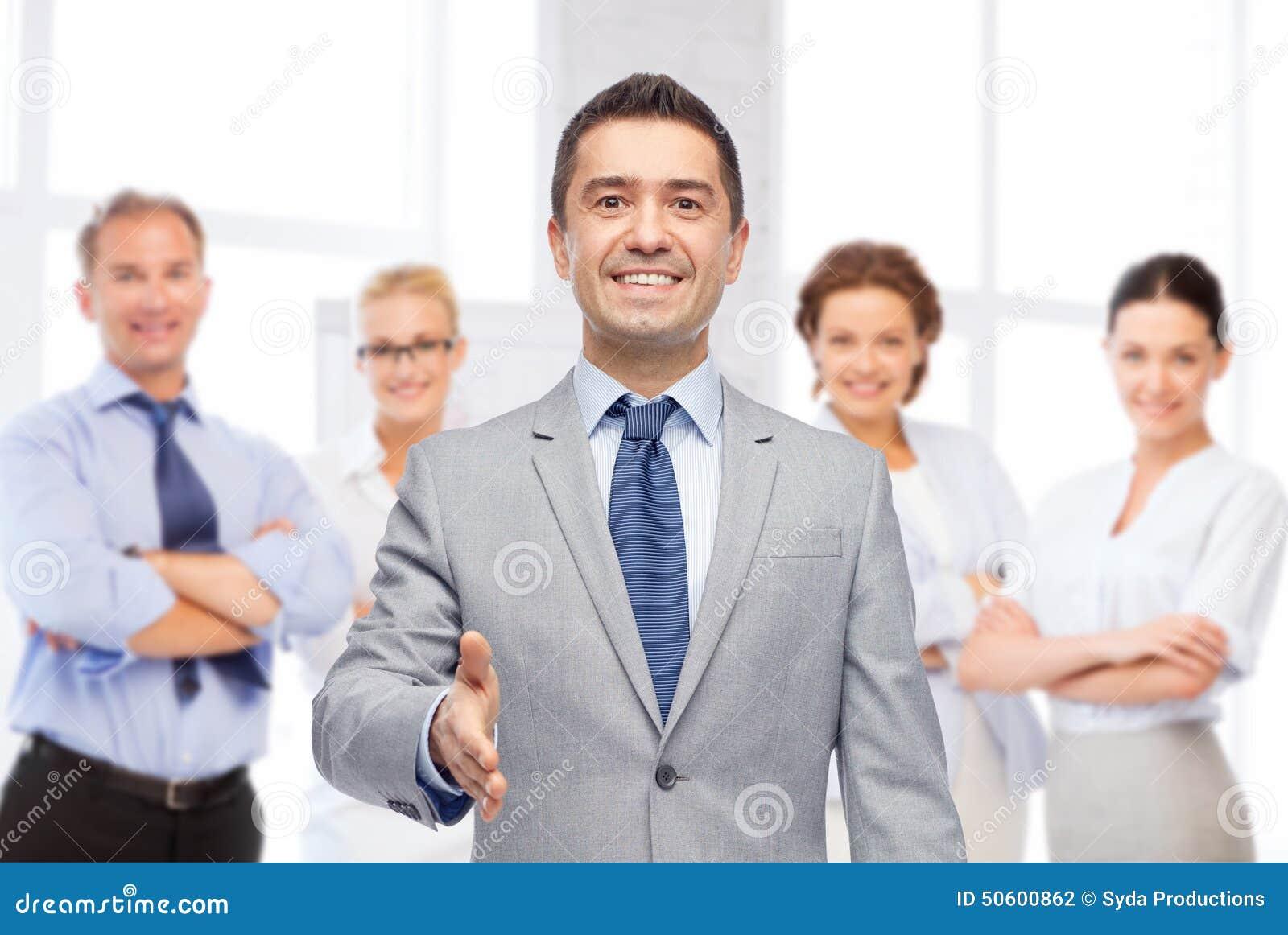 Счастливый усмехаясь бизнесмен в костюме тряся руку