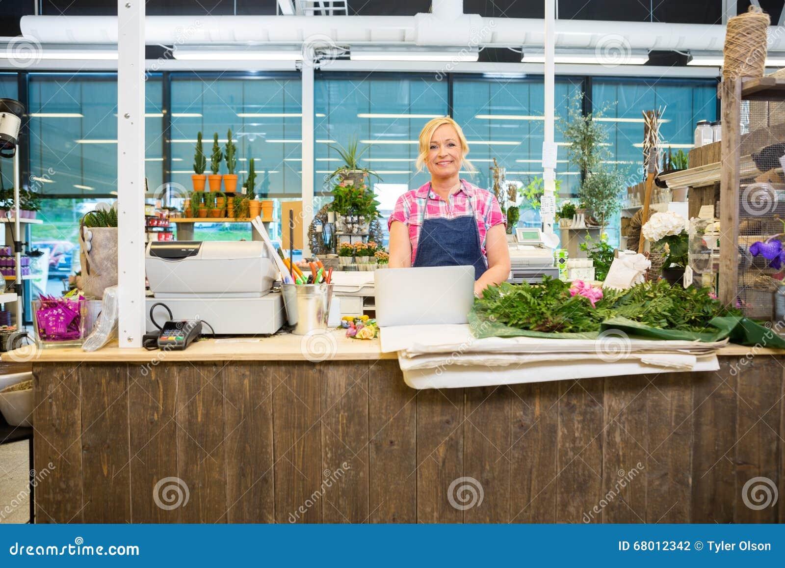 Счастливый флорист стоя на счетчике магазина цветка