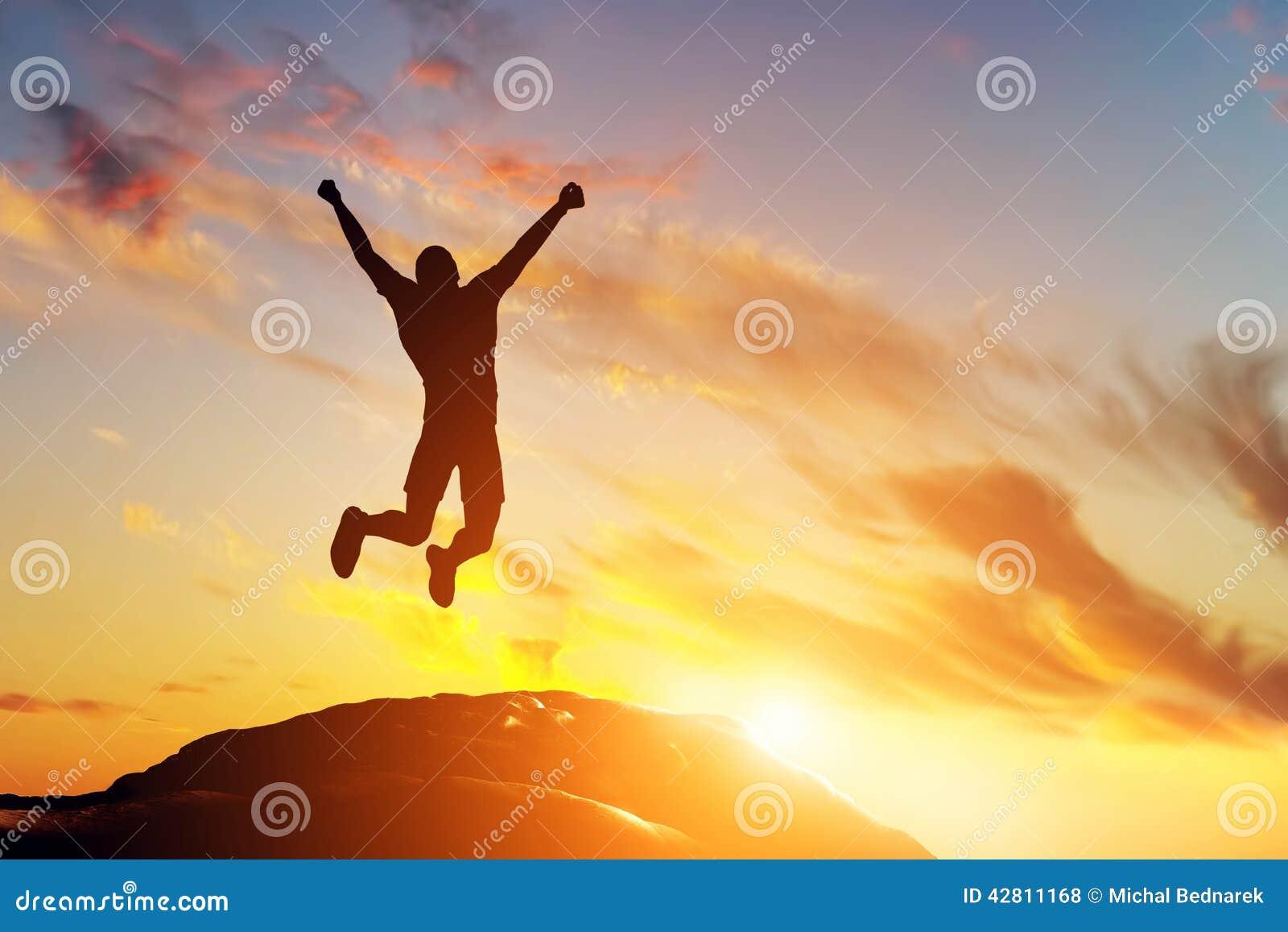 Счастливый человек скача для утехи на пике горы на заходе солнца Успех