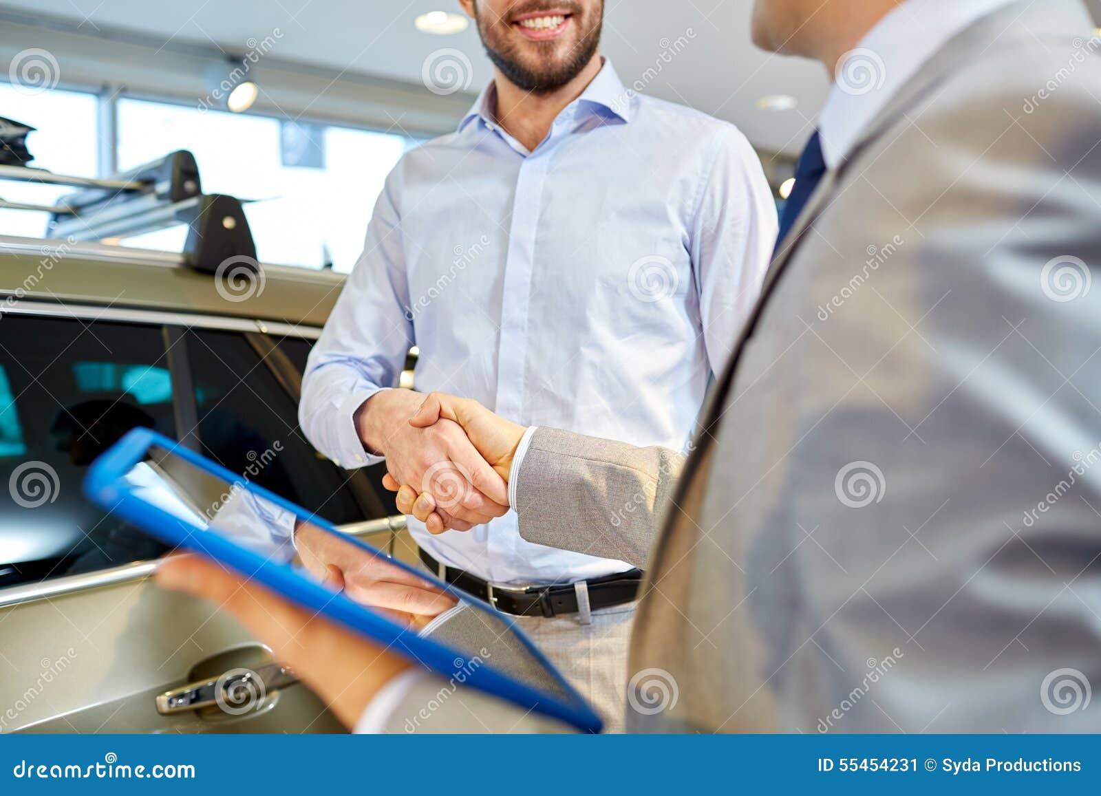 Счастливый человек тряся руки в автосалоне или салоне