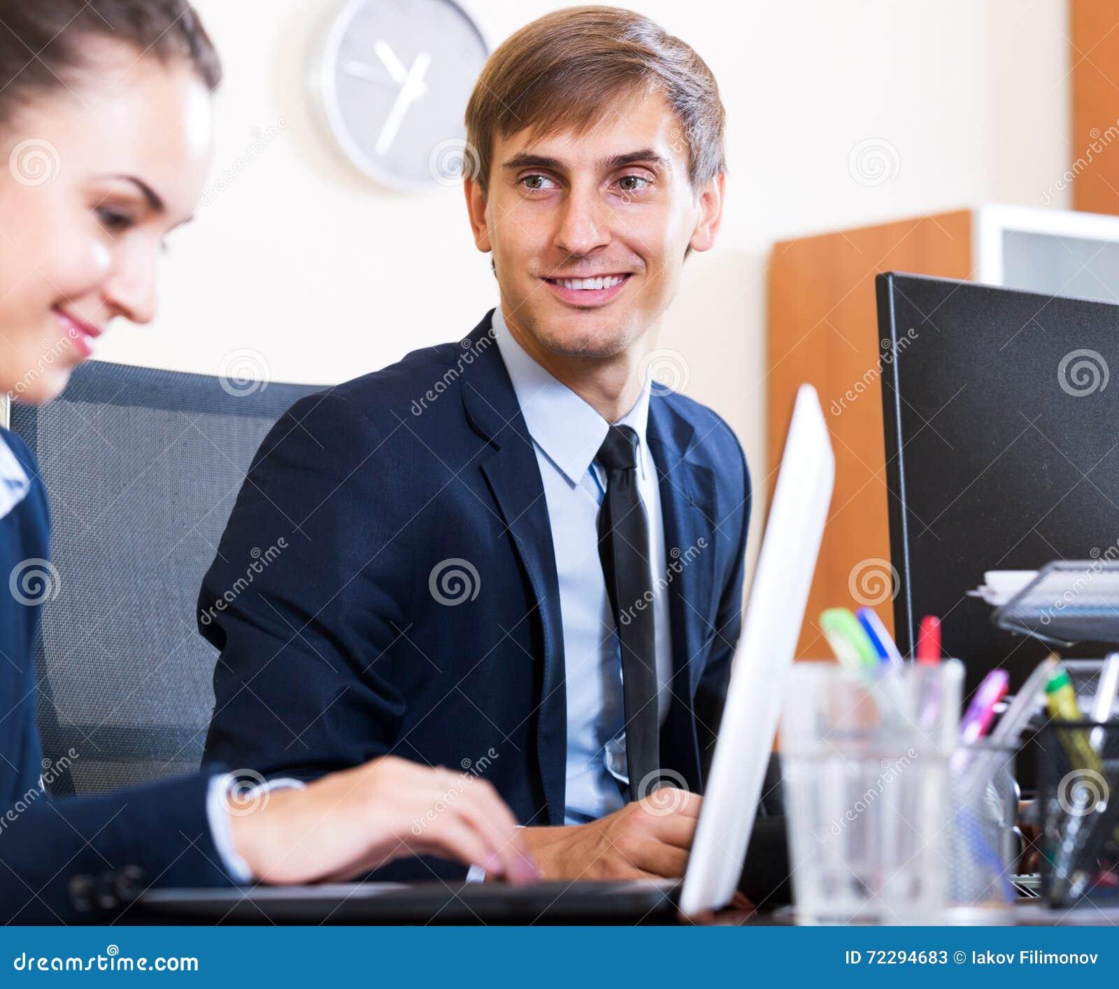 Download 2 счастливых работника в офисе Стоковое Изображение - изображение насчитывающей костюмы, американская: 72294683