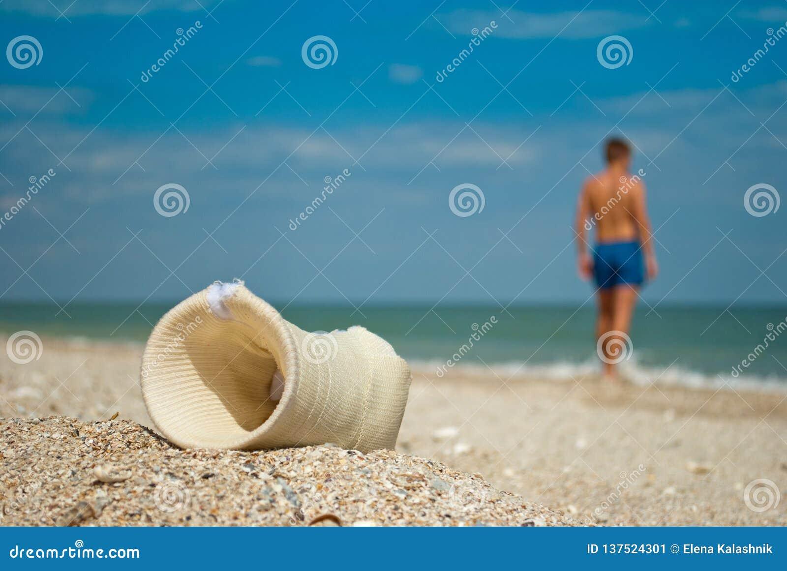 Съемка гипса, конец песка человека вверх против моря и небо, заволакивает сломленный лимб руки, спасение, листья парня