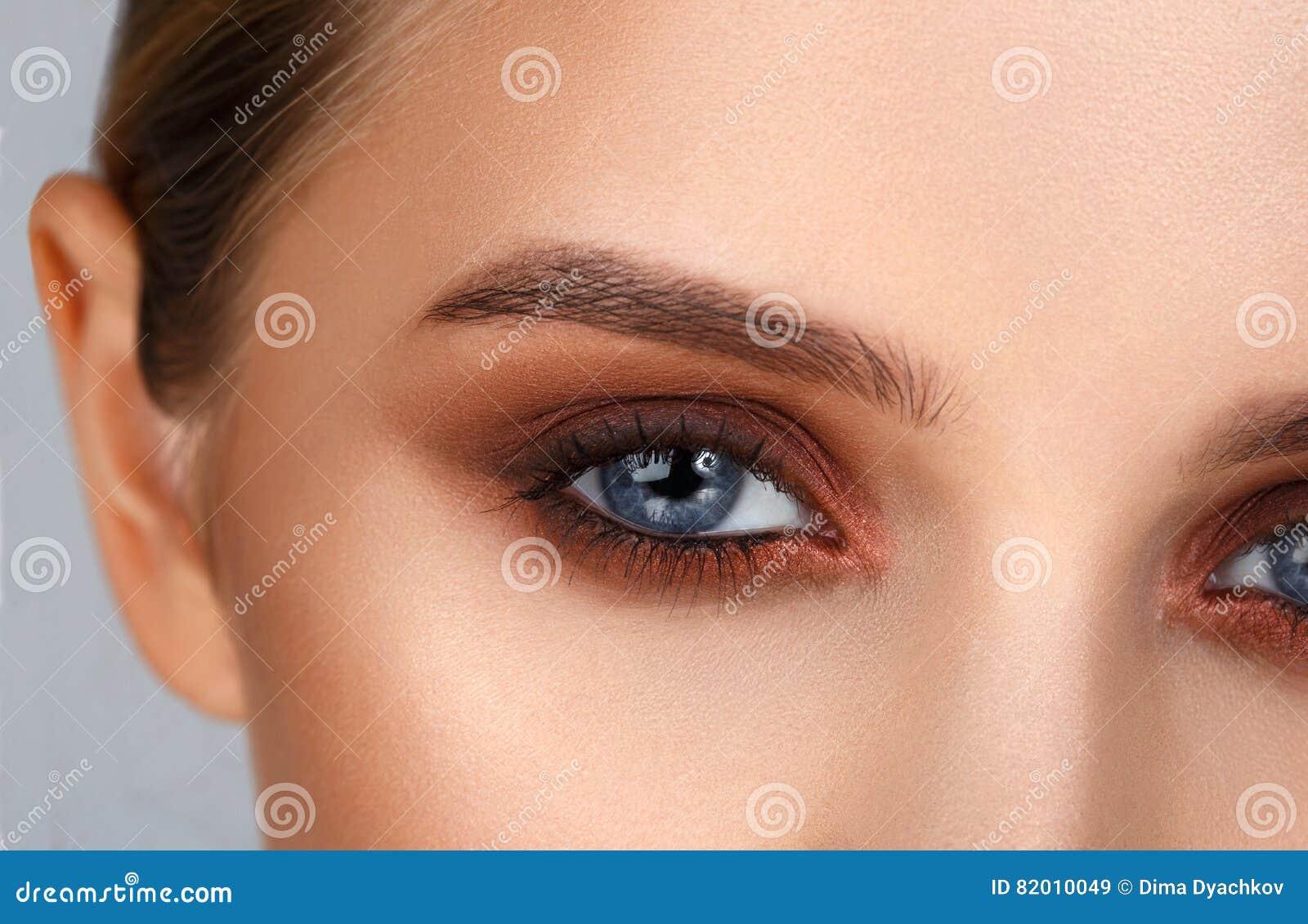 Съемка конца-вверх женского состава глаза в закоптелом стиле глаз
