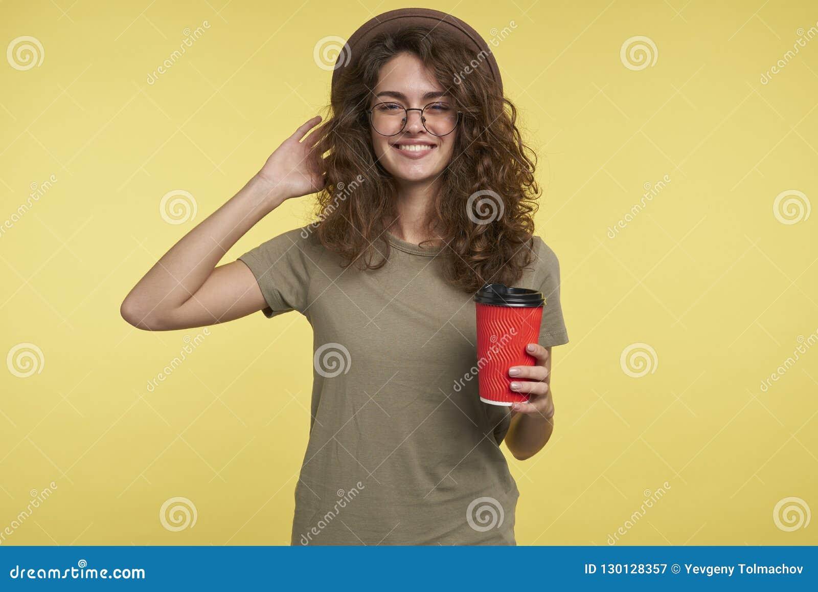Съемка студии молодой женщины студента, она усмехается и держащ кофейную чашку, нося шляпу и eyeglasses, изолированными сверх