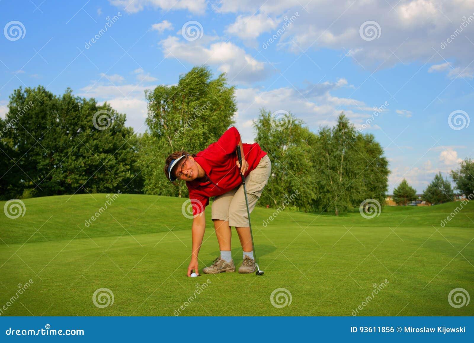 Сыграйте в гольф, игрок в гольф женщины принимая вне шарик от отверстия