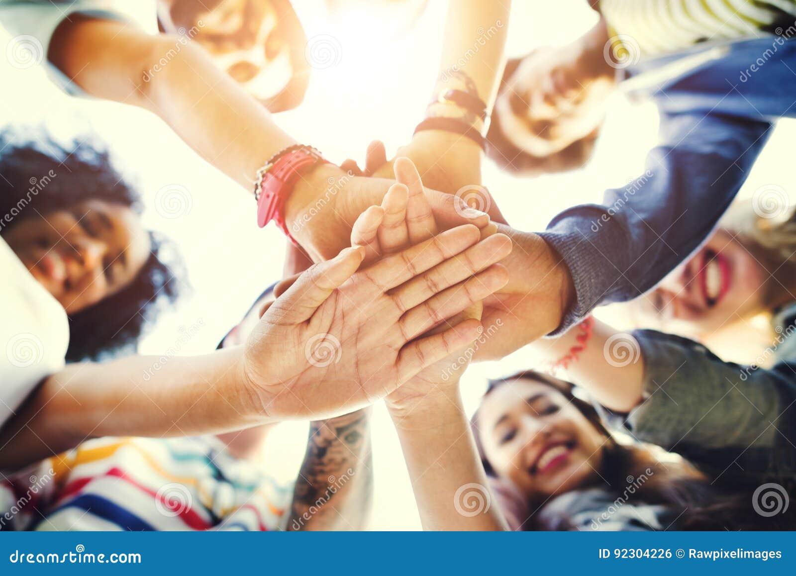 Сыгранность студентов колледжа штабелируя концепцию руки